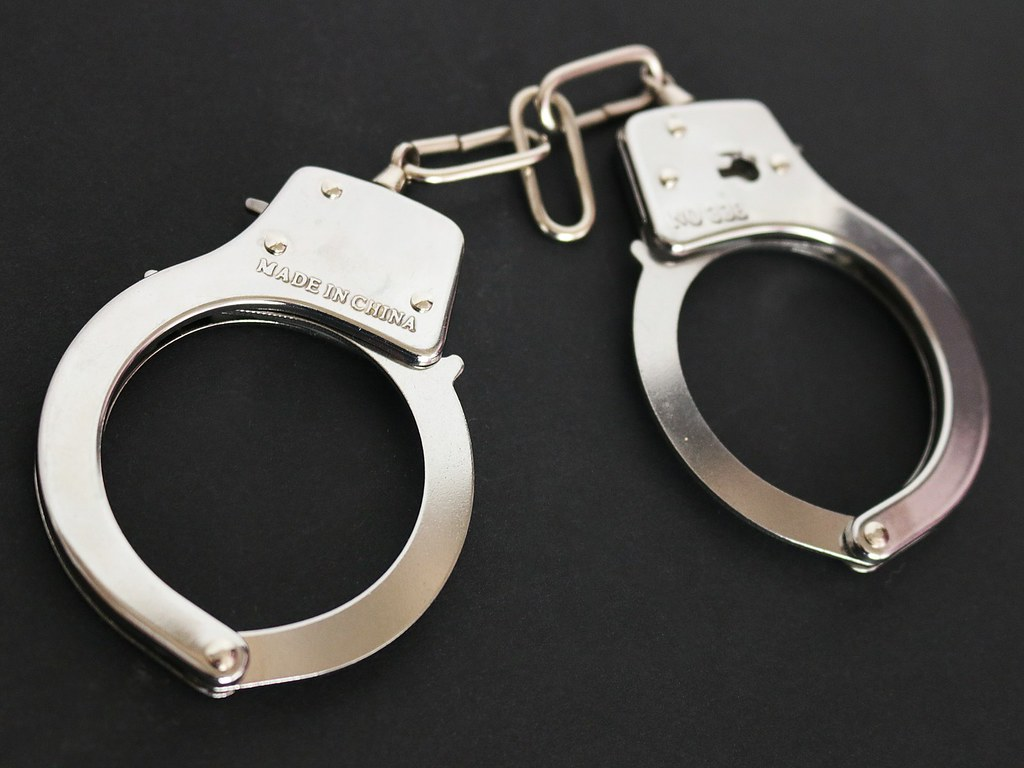 """""""Handcuffs with black background"""" by JobsForFelonsHub is licensed under CC BY 2.0"""